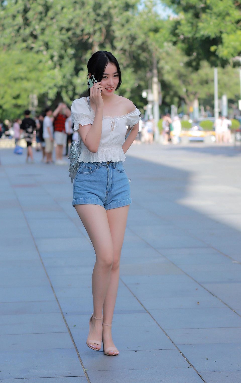 美女用脚�zo��i-_这位打电话的美女身穿一件白色的露肩上衣,搭配牛仔短裤,脚上是一双裸