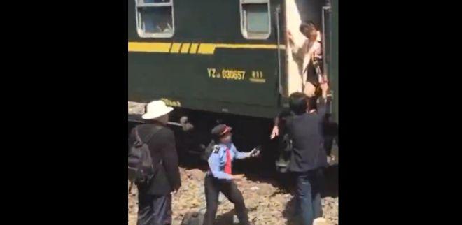 """列车员让乘客跨过铁轨上站台?官方称列车""""因故""""停在轨道中间"""