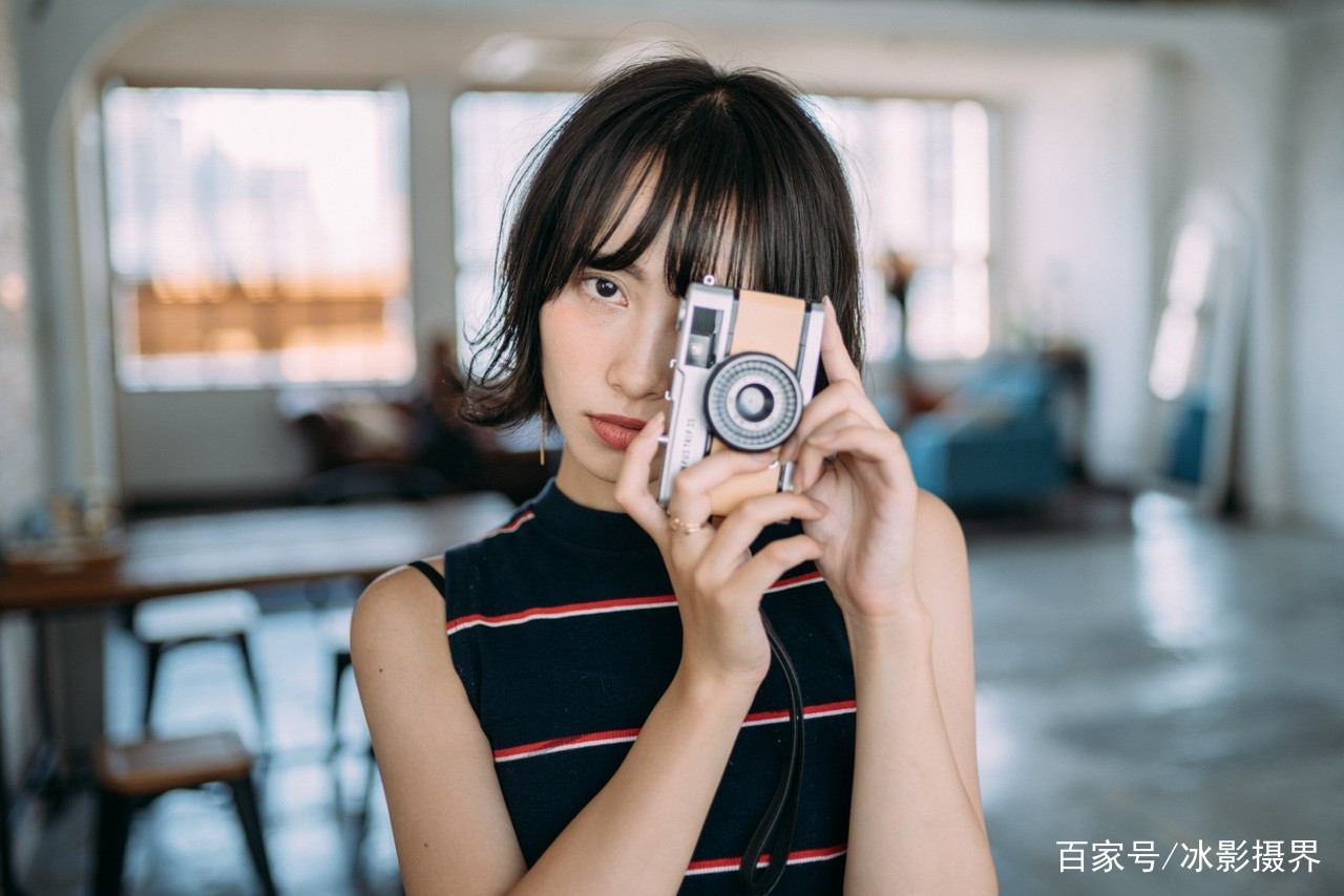 房间里一个手持相机摆拍的气质短发美女图片