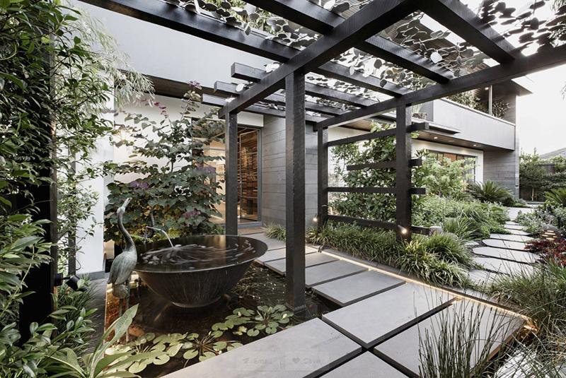 以黑灰色调为主色调的庭院设计,石板路围绕鱼池而设,一路走来,可见水图片