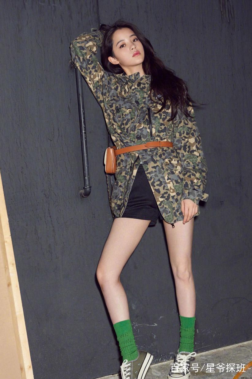 欧阳娜娜身穿墨绿色迷彩斑纹外套,搭配黑色短裤,秀出迷人的长腿,凸显图片