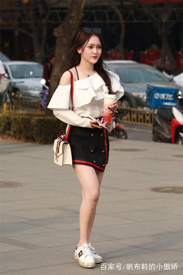 小姐姐身穿白色露肩吊带,搭配黑色不规则齐臀裙,白色松糕鞋,长发飘飘