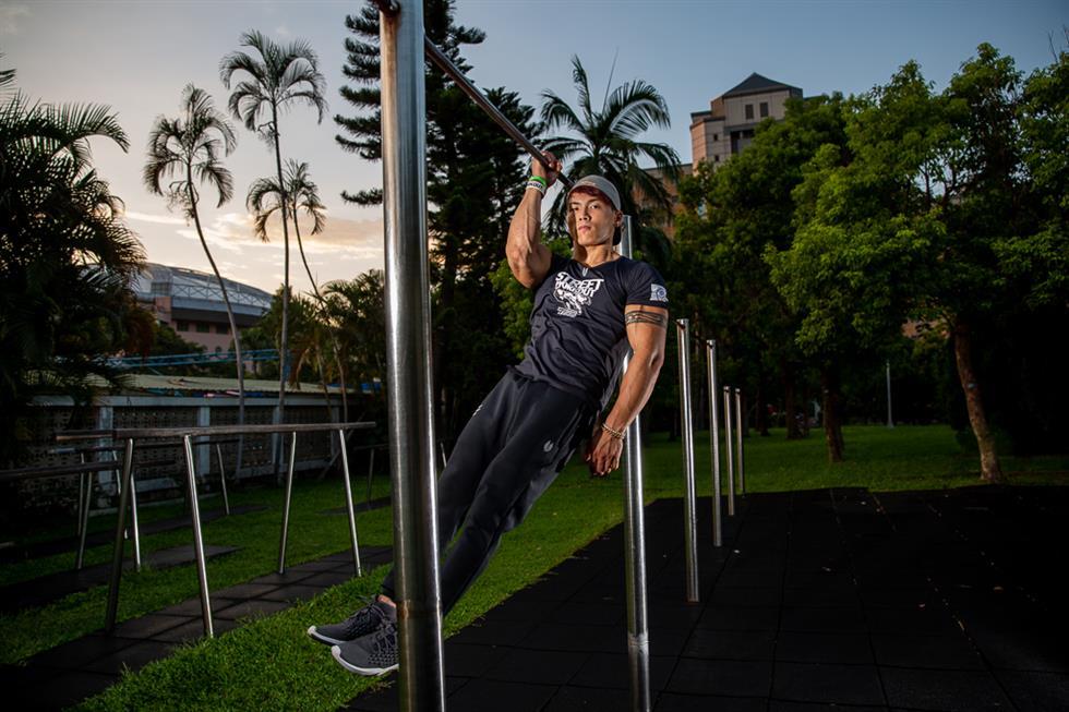 你有没有看过街头健身的超酷玩家,他们就像体操运动员一样,在单杠,双杠以及地上,作者超乎常人的酷炫动作?你曾几何时有没有想过可以跟那些街头健身玩家一样,做很多帅气又厉害的,超酷的健身动作?很多男生应该都想过,但是最后因为各种原因不了了之。而来自台湾的街头健身常胜将军林立新,是一个心动不如行动的实际派。  现年22岁的林立新,看起来壮硕而沉稳。6年前因为误打误撞进入街头健身圈,那个时候他还在读高中,没有接触任何运动的他被同学拉去参加跑酷练习会,在休息的时候看到有人玩人体旗帜等酷炫的健身动作,他觉得做出这