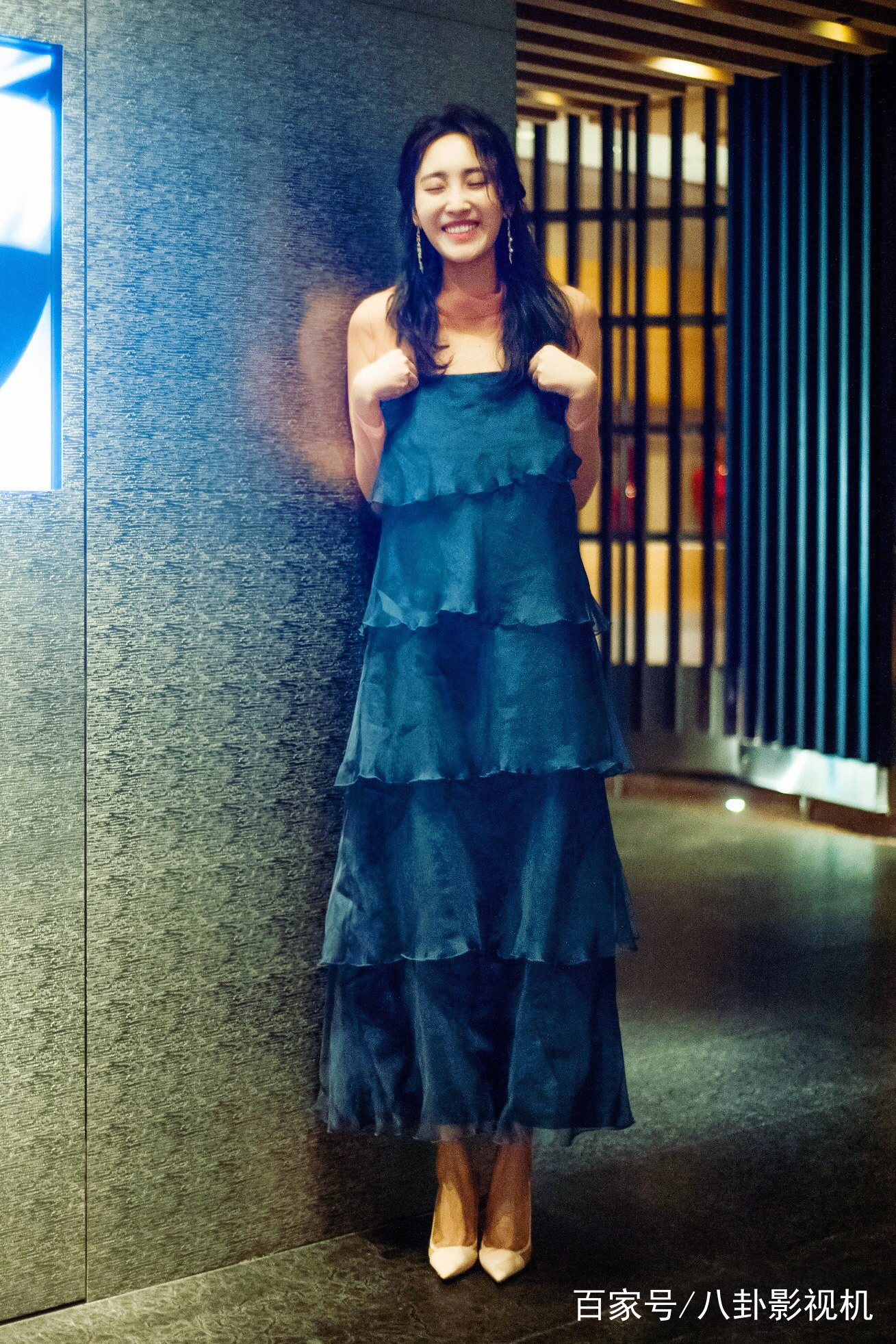 穿着一袭深蓝色的裙子搭配白色的高跟鞋,灿烂的笑容,闭着眼睛活泼可爱
