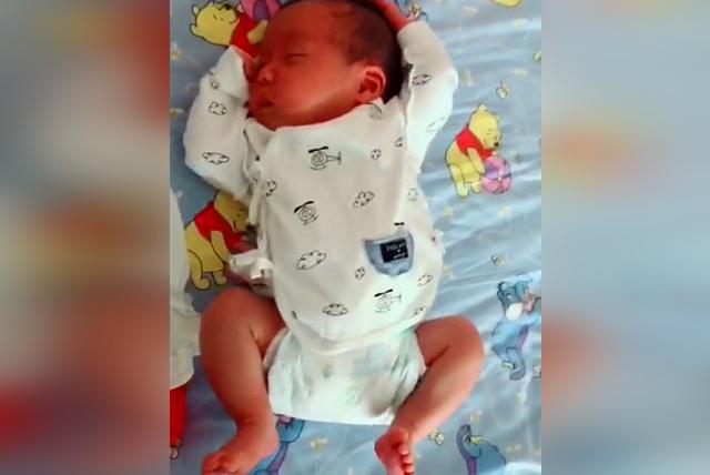 宝宝刚出生13天,在睡觉的时候突然把耳朵捂住了,网友:小可爱