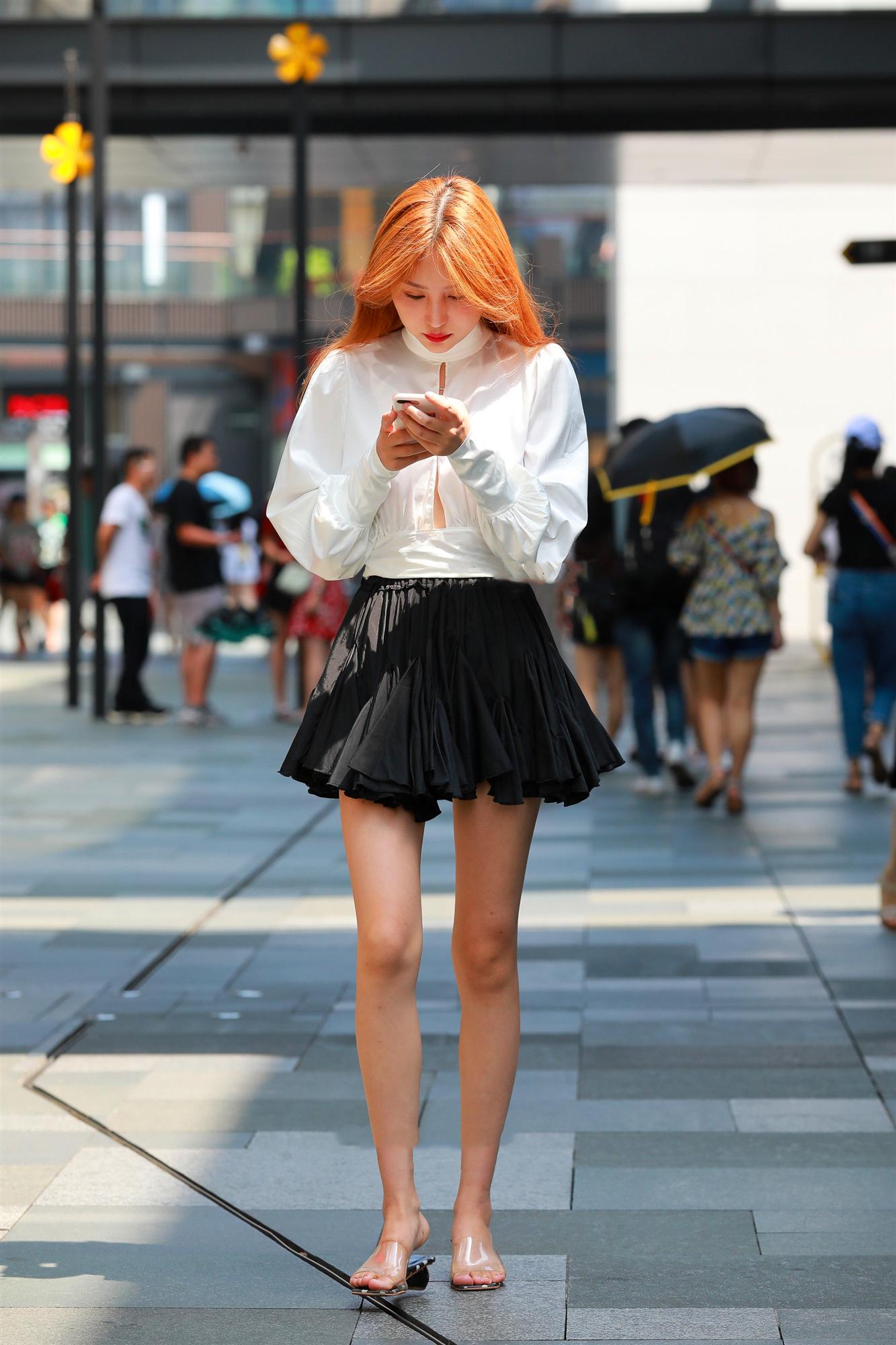 黄色长发气质美女,身穿白色休闲上衣,搭配黑色百褶裙,透明高跟鞋,轻松