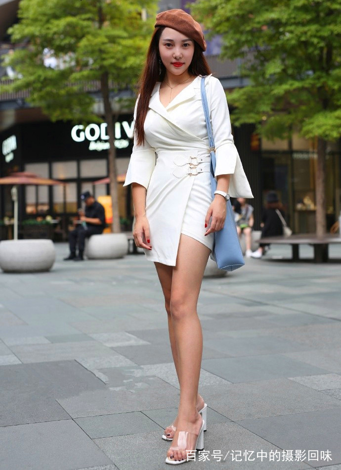 长发飘飘气质美女身穿白色低胸齐臀裙,搭配透明高跟鞋,秀出白皙大长腿