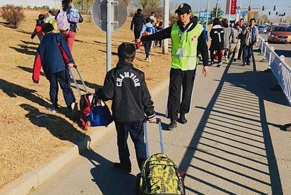 北京顺义区火沙路部分路段封闭改造,校车遇阻,学生车流间穿行
