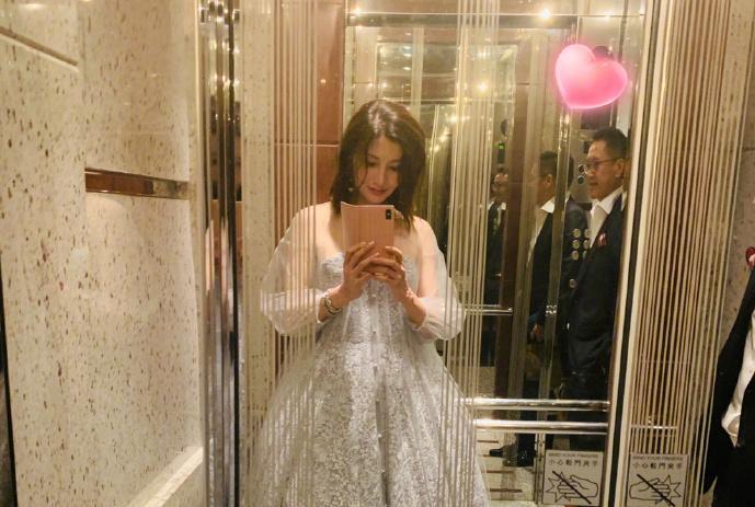 李嘉欣身着薄纱公主裙,在电梯中着迷自拍,许晋亨贴墙站让出空间