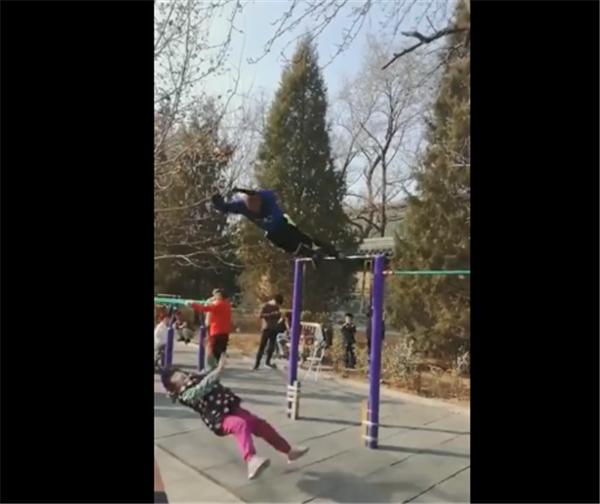大爷在公园倒挂单杠,做脚回环顶飞小女孩,杠友:这纯属