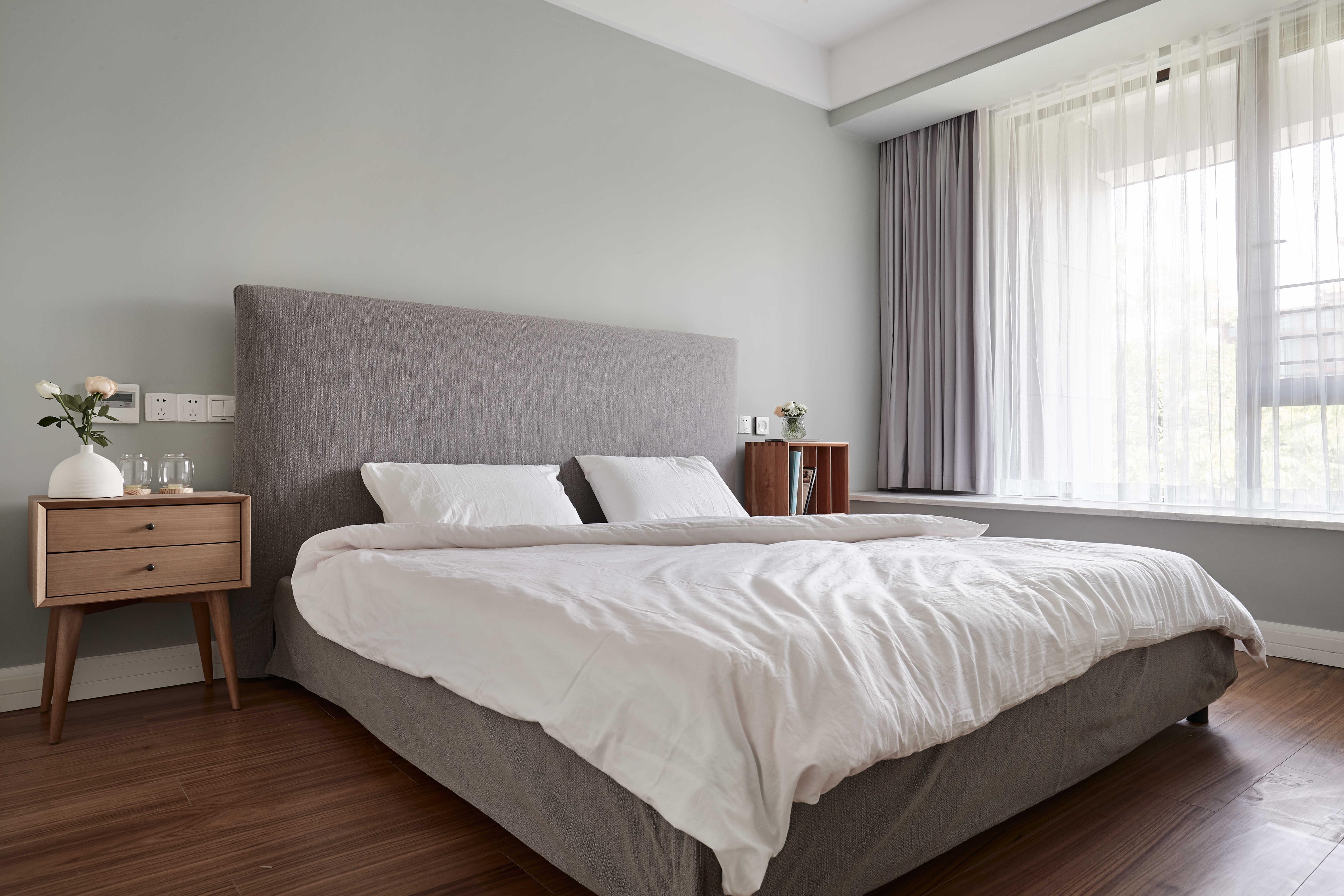 卧室墙壁的颜色与客厅沙发的一样,抹茶色墙壁,灰色大床,木纹地板,色彩图片