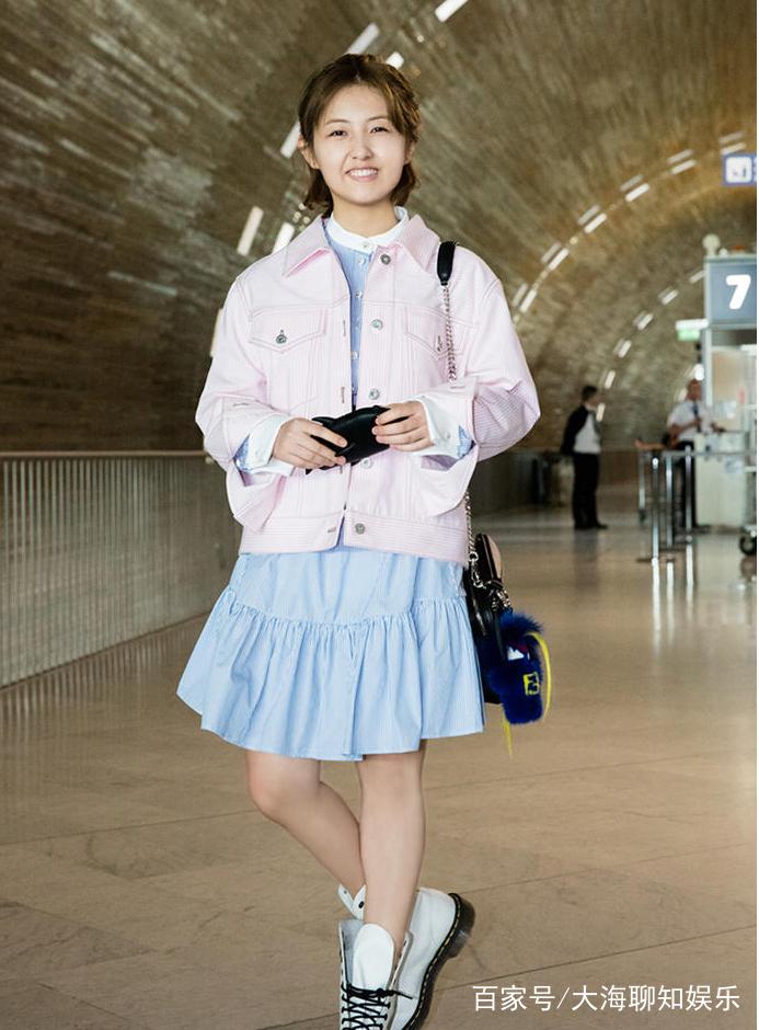 张子枫身穿蓝色短袖,搭配黑色裤子,背着斜挎包,充满少女气息