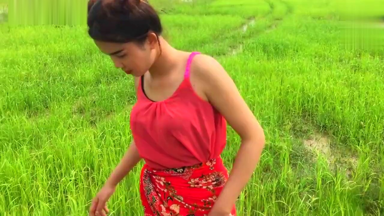 农村可爱美女田里游玩,用手随便一捞就抓到大鱼,高兴地合不拢嘴