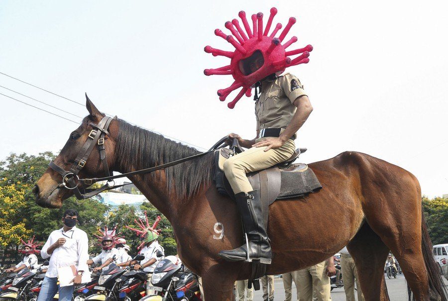 An Indian policeman wearing a virus-themed helmet rides on a horse during an awareness rally in Hyderabad on April 2, 2020.
