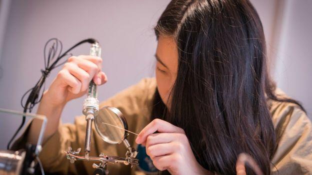 Young maker Tina Jiang soldering.