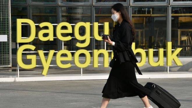 A woman wearing a protective face mask, as a preventative measure against the COVID-19 coronavirus, walks near Dongdaegu railway station in Daegu, on February 26, 2020