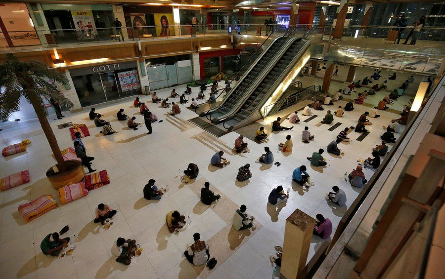 Migrant workers eat their dinner inside a shopping mall turned into a shelter during a 21-day nationwide lockdown to slow the spreading of coronavirus in Ahmedabad on April 7, 2020.