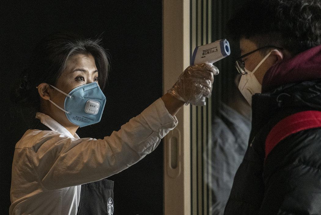 一月,北京一座机场内的星巴克员工在给顾客量体温。