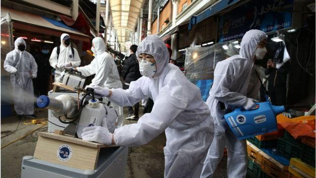 Disinfection professionals wearing protective gear spray anti-septic solution against the coronavirus (COVID-19) at a traditional market on February 26, 2020 in Seoul, South Korea