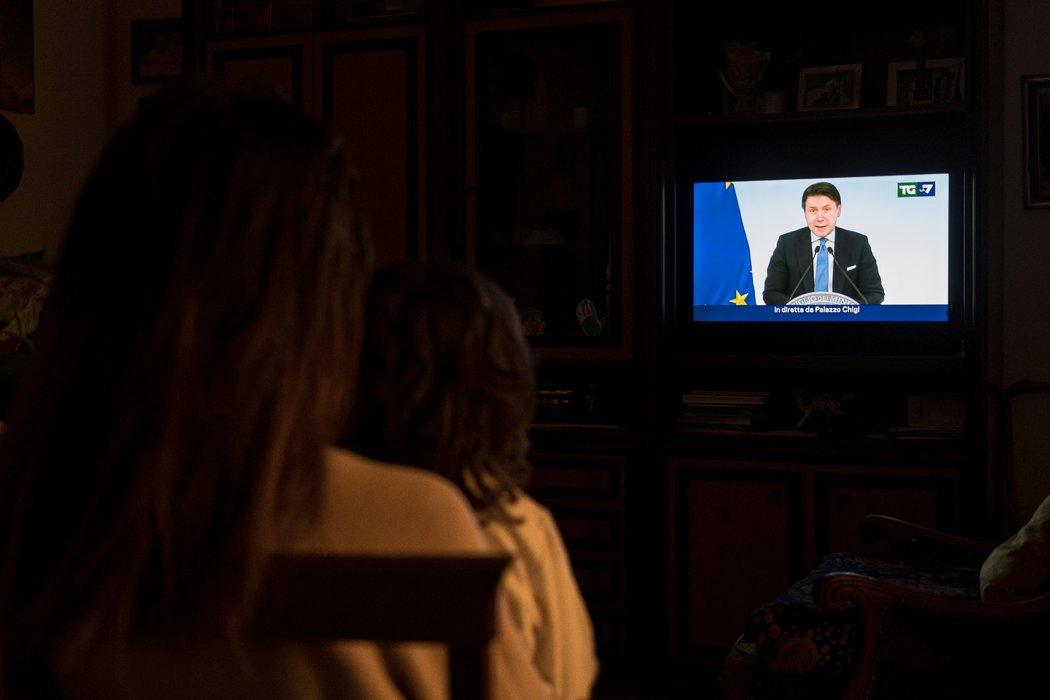 """圣菲奥拉诺市民观看意大利总理朱塞佩·孔特宣布全国实施旅行禁令。这里是最早实行封锁措施的""""红色地带""""的城镇之一。"""