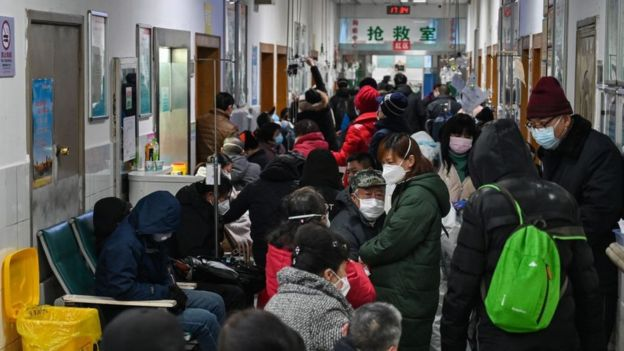 People wearing facemasks to help stop the spread of a deadly virus which began in the city, wait for medical attention at Wuhan Red Cross Hospital in Wuhan on January 25, 2020.
