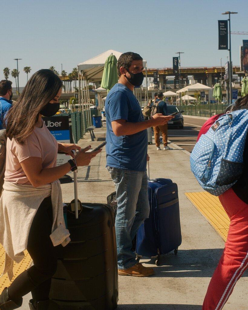 上个月,洛杉矶国际机场的旅客在机场接送点等待他们叫的车。