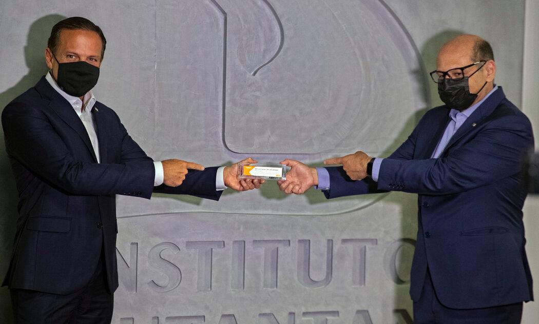 圣保罗州长若昂·多利亚(左)和负责协调新冠病毒疫苗试验的巴西医学研究所所长迪马斯·科瓦斯向人们展示一盒试验疫苗。