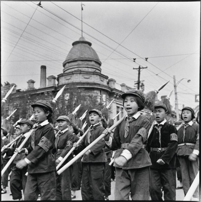 1966年,扛着红缨枪、佩戴红袖章的学童游行经过哈尔滨一家俄罗斯风格的百货商店。