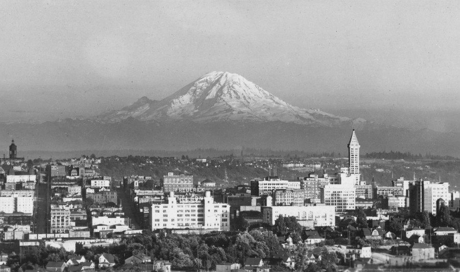 A view of Mount Rainier, with the buildings of Seattle, Washington, visible in the foreground, in 1921. This photo was taken from Bigelow Avenue, North, near present-day Bhy Kracke Park. See the view today in Google Maps.