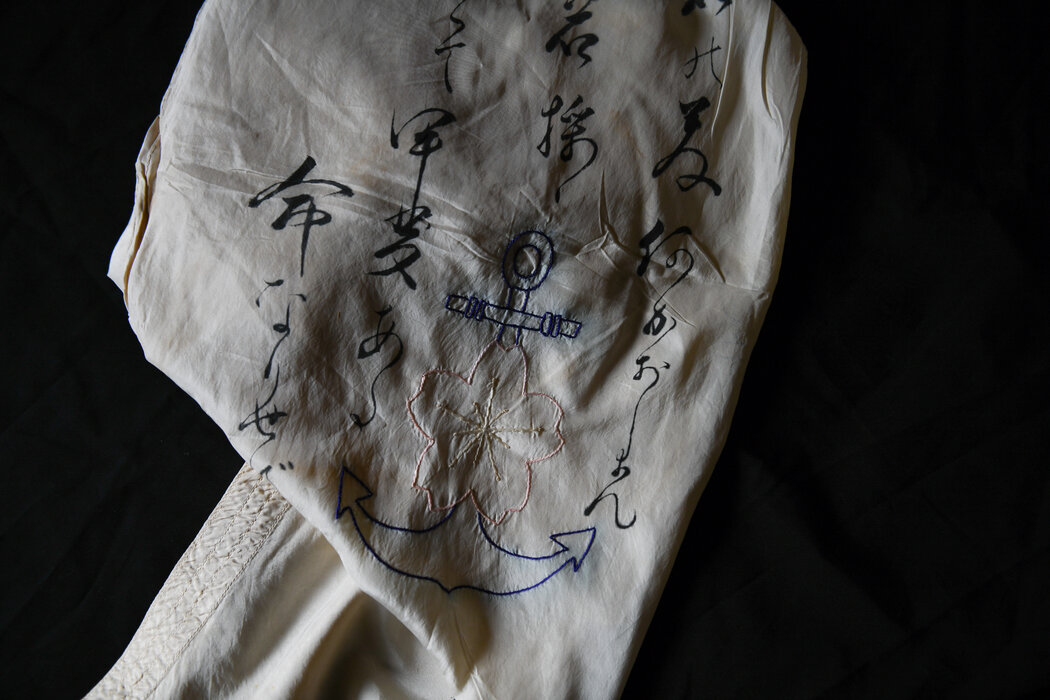 """大馆和夫在""""二战""""中执行任务时戴的丝巾。它是用降落伞布做的,上面绣着他所在部队的象征:樱花和蓝猫。"""