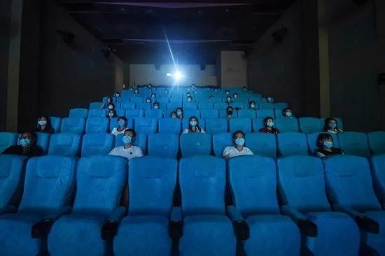 中国杭州电影院的观众遵循新的规范:保持距离,佩戴口罩。来源:AFP/Getty。