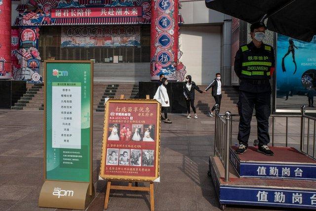 北京一个打疫苗享优惠布告牌边,一家国有照相馆打出了为接种新冠疫苗者拍婚纱照享九折优惠的广告。