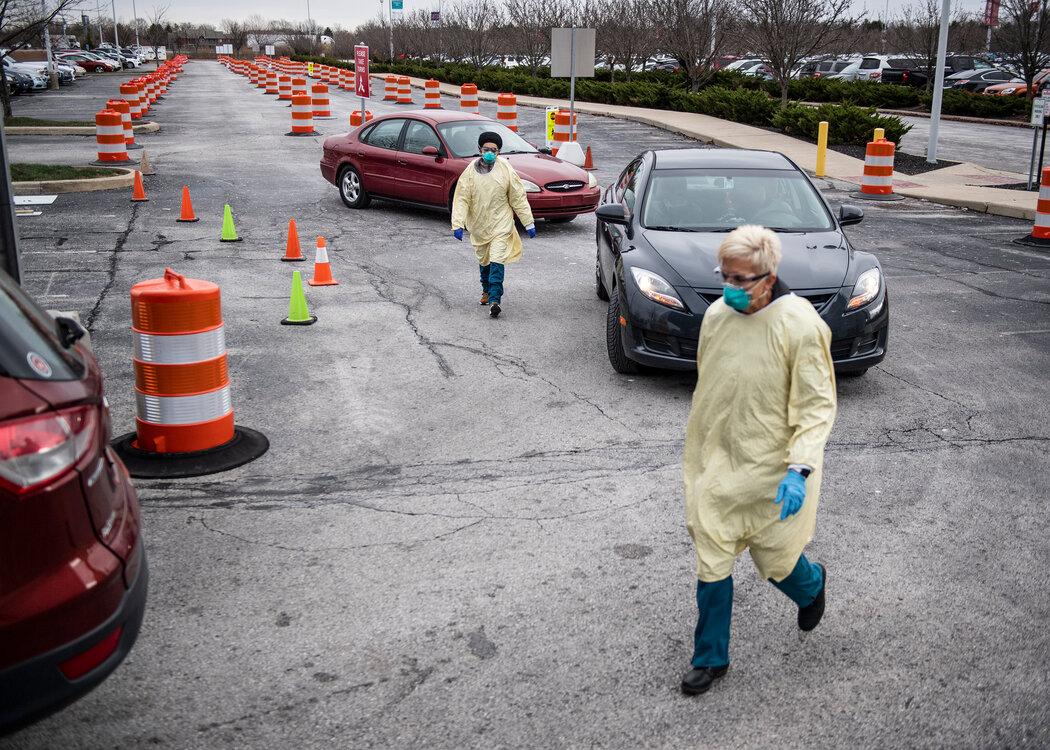 本月初,印第安纳州印第安纳波利斯一个免下车检测点的工作人员。许多中国人将美国对待大流行的方式视为他们对该国心态的转折点。