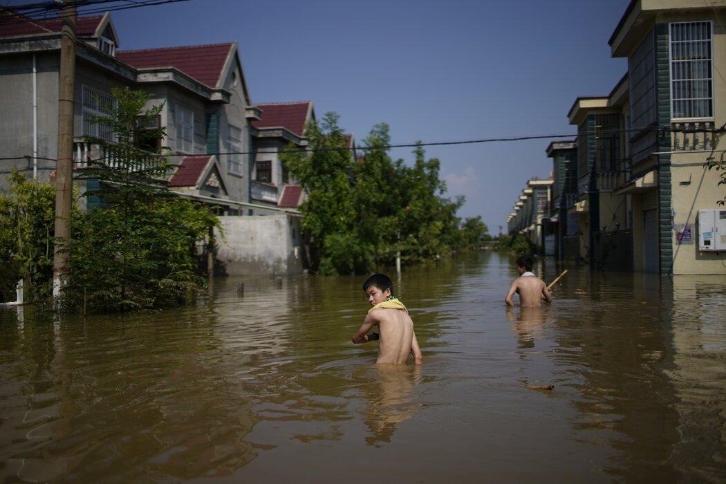 周六,中国新乡,孩子们在洪水中蹚水前行。