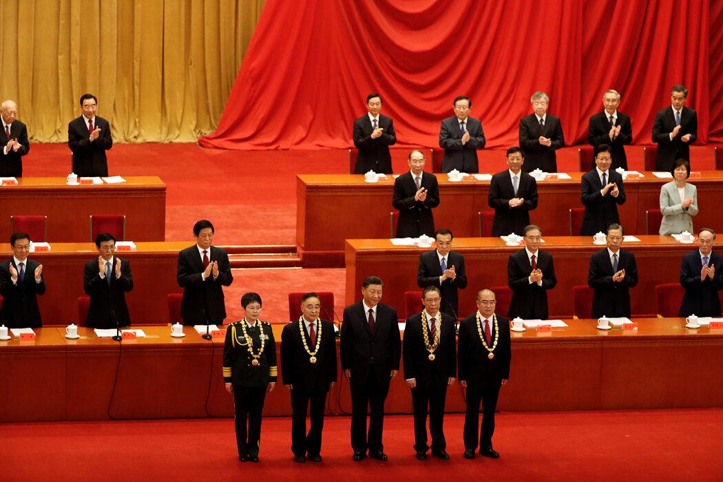 9月,在表彰官员抗击新冠病毒的大会上,习近平(中)与钟南山(右二)等受勋者合照。