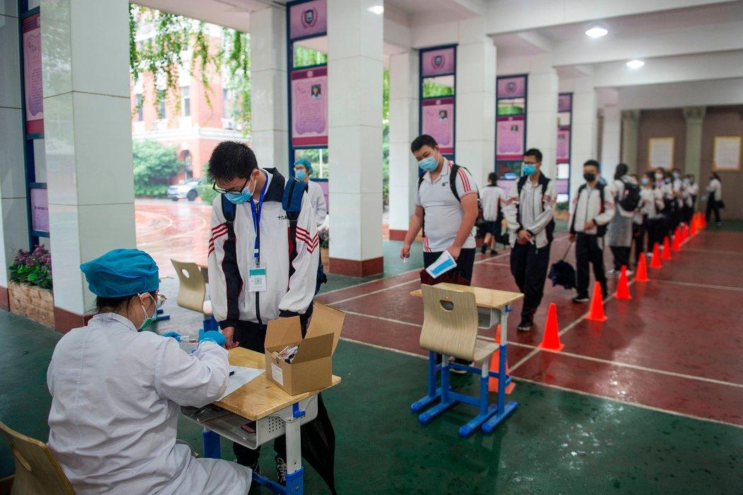 周四,武汉一所学校的学生排队做拭子采样。