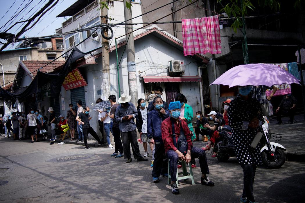 上个月,疫情暴发地武汉的一处居民区,人们等待接受新冠病毒检测。