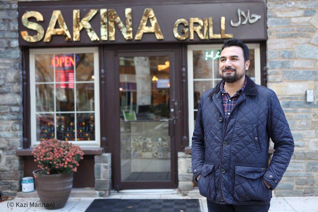 卡兹·曼南站在他的餐馆外。