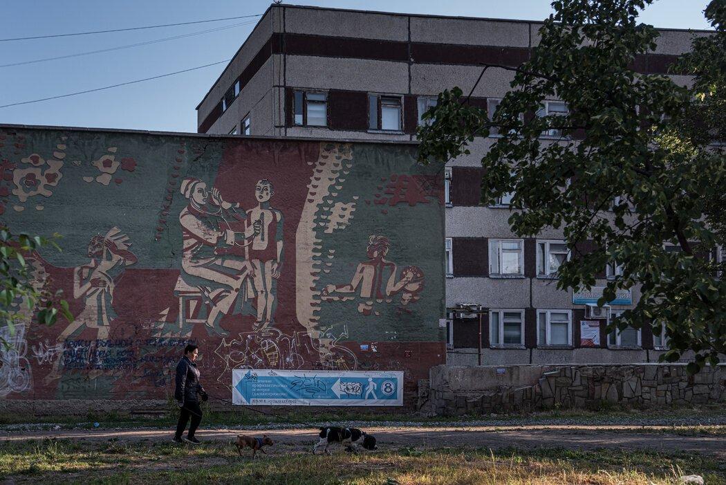 一幅壁画上,医生在诊所外照顾儿童,该地区有人因实验室泄漏而丧生。