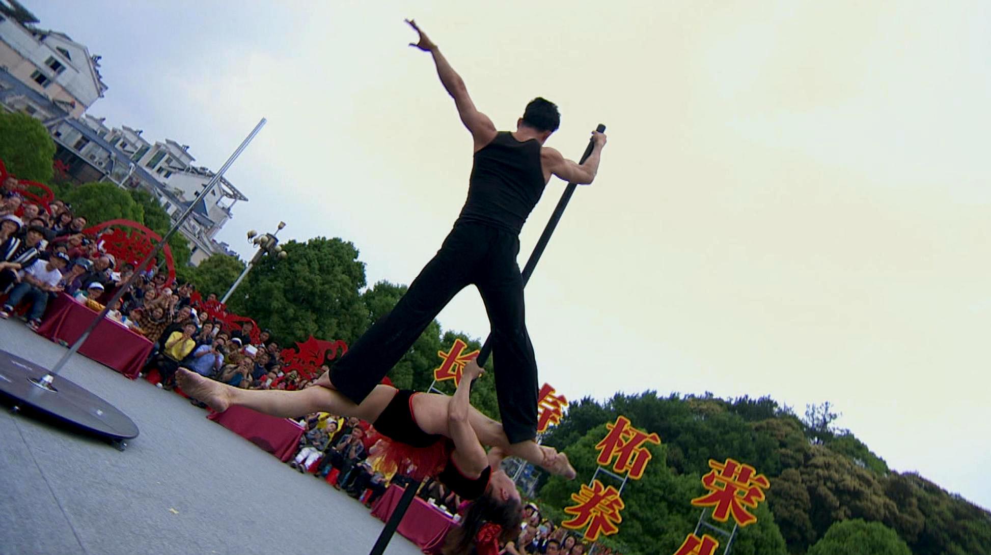 50岁大妈展示舞技,唯美演绎高难度钢管舞动作,瞬间惊艳围观人群
