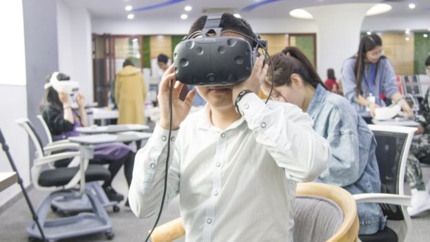 A man wears a virtual reality headset for the See For She experience.
