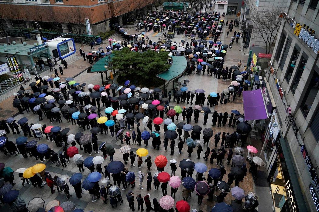 上个月,人们在首尔排队买口罩。